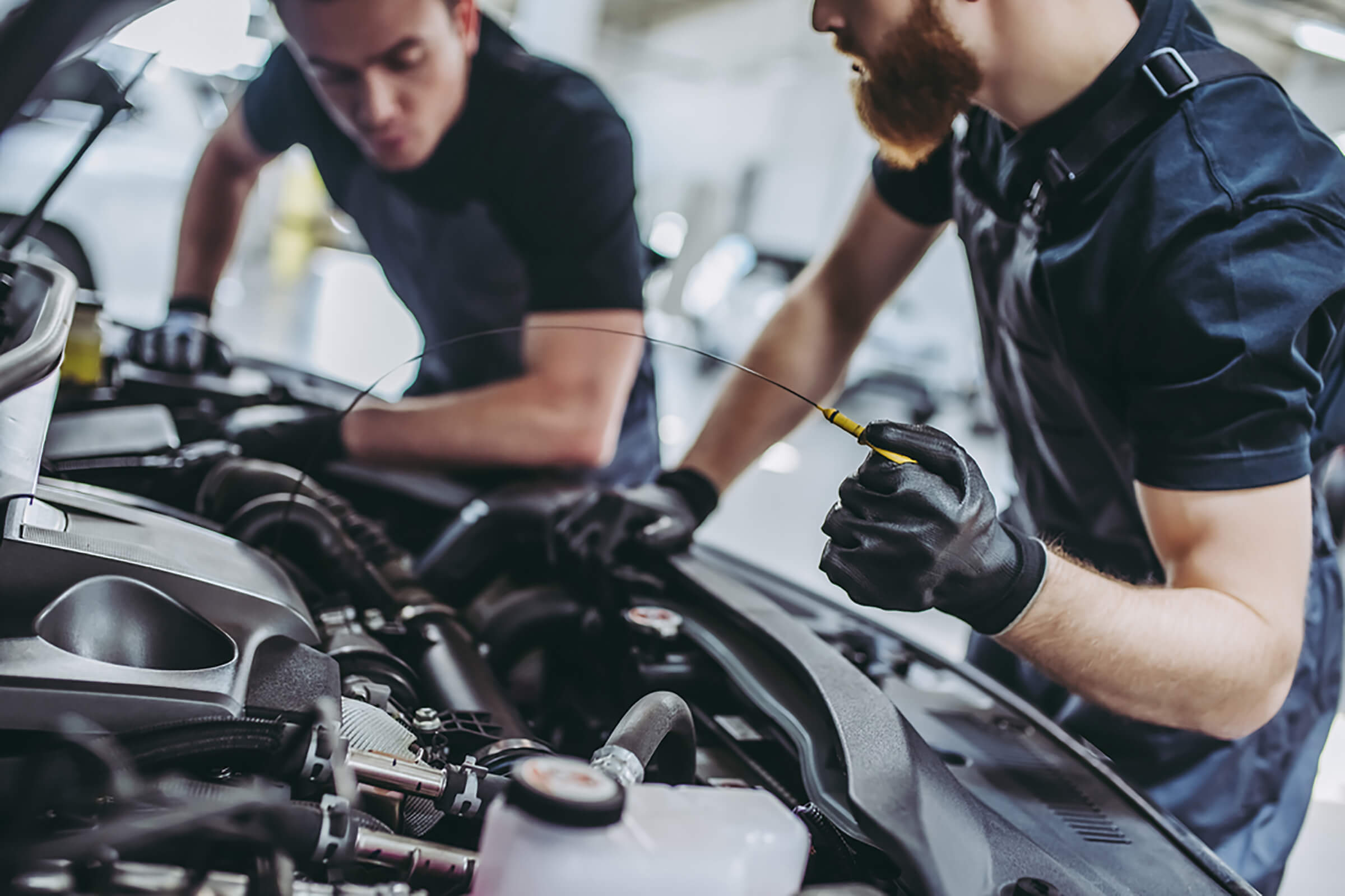 Cropped image of two handsome mechanics in uniform are working in auto service. Car repair and maintenance. Checking the oil level.; Shutterstock ID 727443778